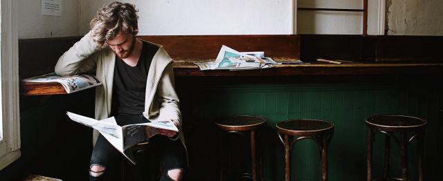 Elite, jongen leest krant