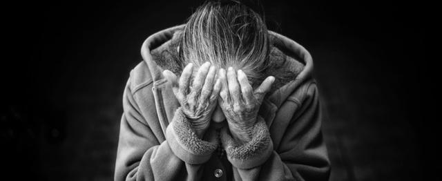 Een oude vrouw begraaft haar gezicht in haar handen