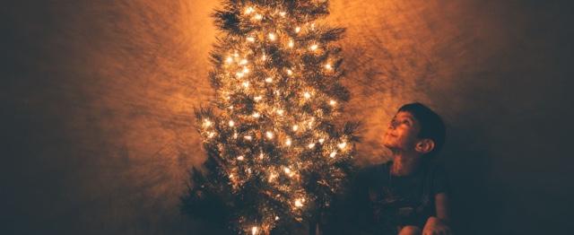 Kerst, jongen bij kerstboom