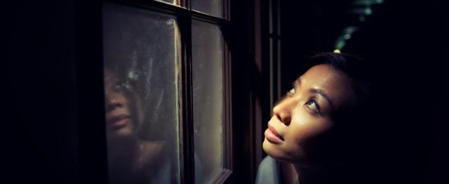Vrouw kijkt uit raam
