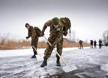 Militair, sneeuw aan het schuiven, elfstedentocht