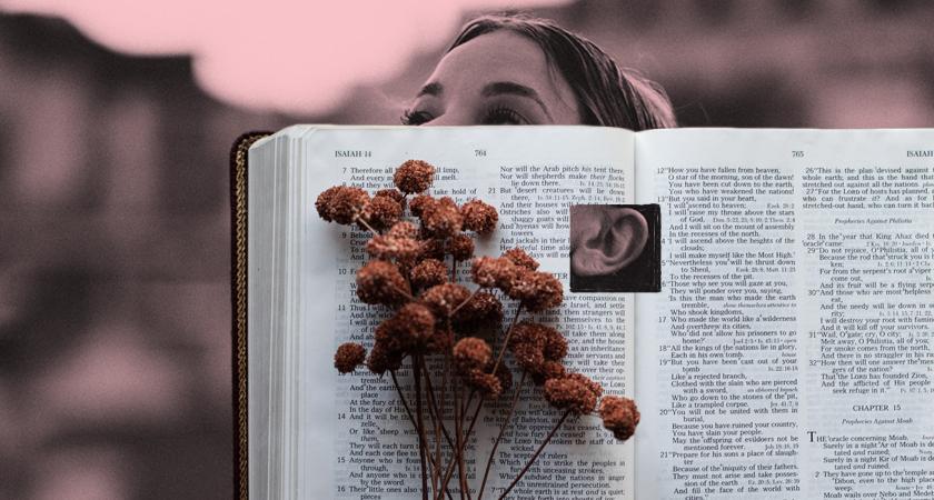 Vrouw met daar overheen een opengeslagen Bijbel. In die Bijbel is een gat geknipt zodat het oor van de vrouw zichtbaar is. Luisteren naar de Bijbel.