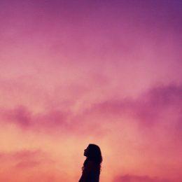 Silhouet van vrouw tegen een paarsgekleurde hemel, de vrouw lijkt eenzaam