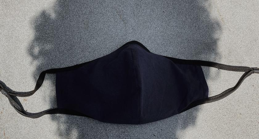 Schaduw van hoofd op de grond, met daar bovenop een mondmasker